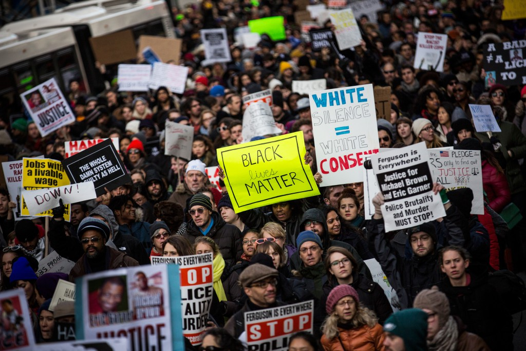 NEW YORK, NY - DECEMBER 13:  People march in the National March Against Police Violence, which was organized by National Action Network, through the streets of Manhattan on December 13, 2014 in New York City. The march coincided with a march in Washington D.C. and comes on the heels of two grand jury decisions not to indict white police officers in the deaths of two unarmed black men.  (Photo by Andrew Burton/Getty Images)